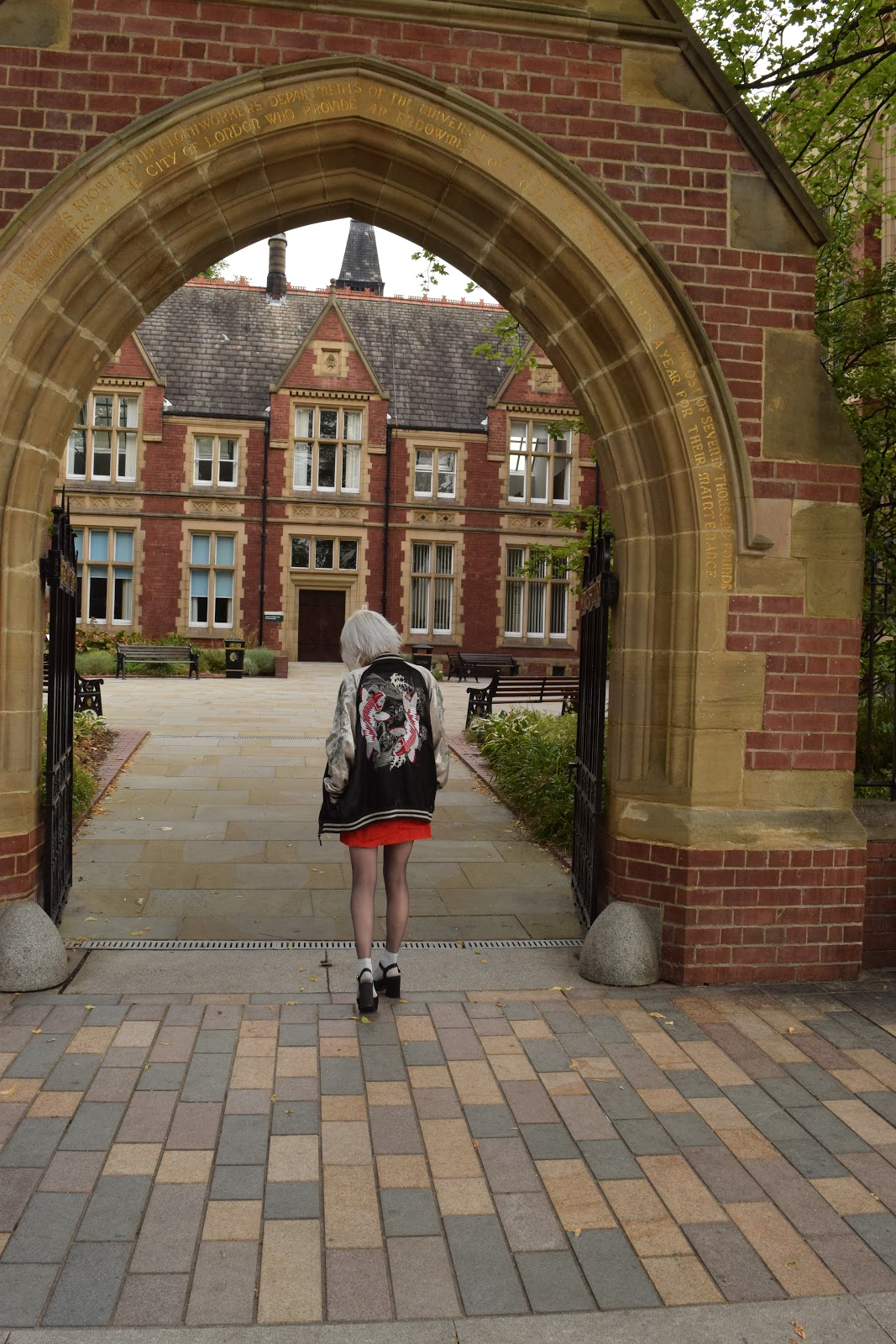 silver haired girl in red dress, heels and sukajan standing in an archway at the University of Leeds