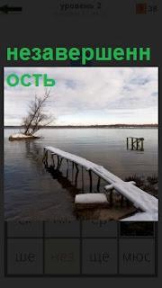 Длинный узкий мостик незавершенный до конца и кругом вода в зимнее время