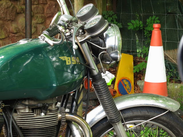Old green motorbike with trees reflected in its petrol tank. No parking cone and red and white traffic cone
