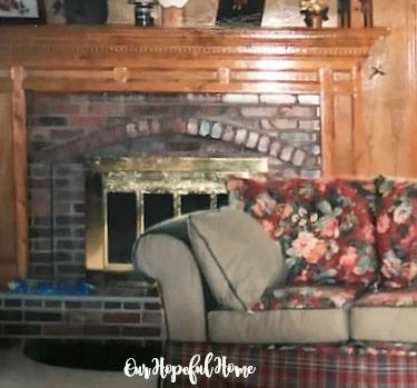 red brick fireplace brass doors wooden mantel