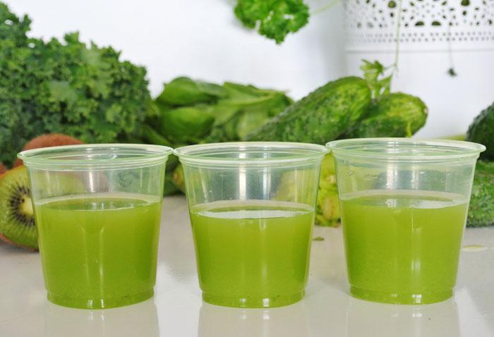 zielony sok w kubeczkach na tle zielonych warzyw