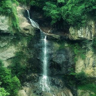 Início da queda d´água da Cachoeira Véu de Noiva, no Distrito de Galópolis, em Caxias do Sul. Árvores nativas ao redor.