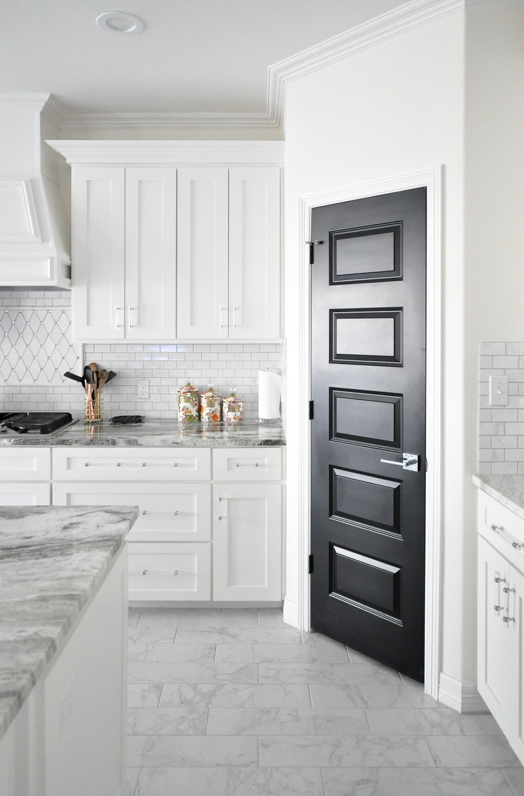 Gorgeous white shaker cabinet kitchen cabinets with lucite hardware and a black pantry door. The marble backsplash and counter tops look so chic!