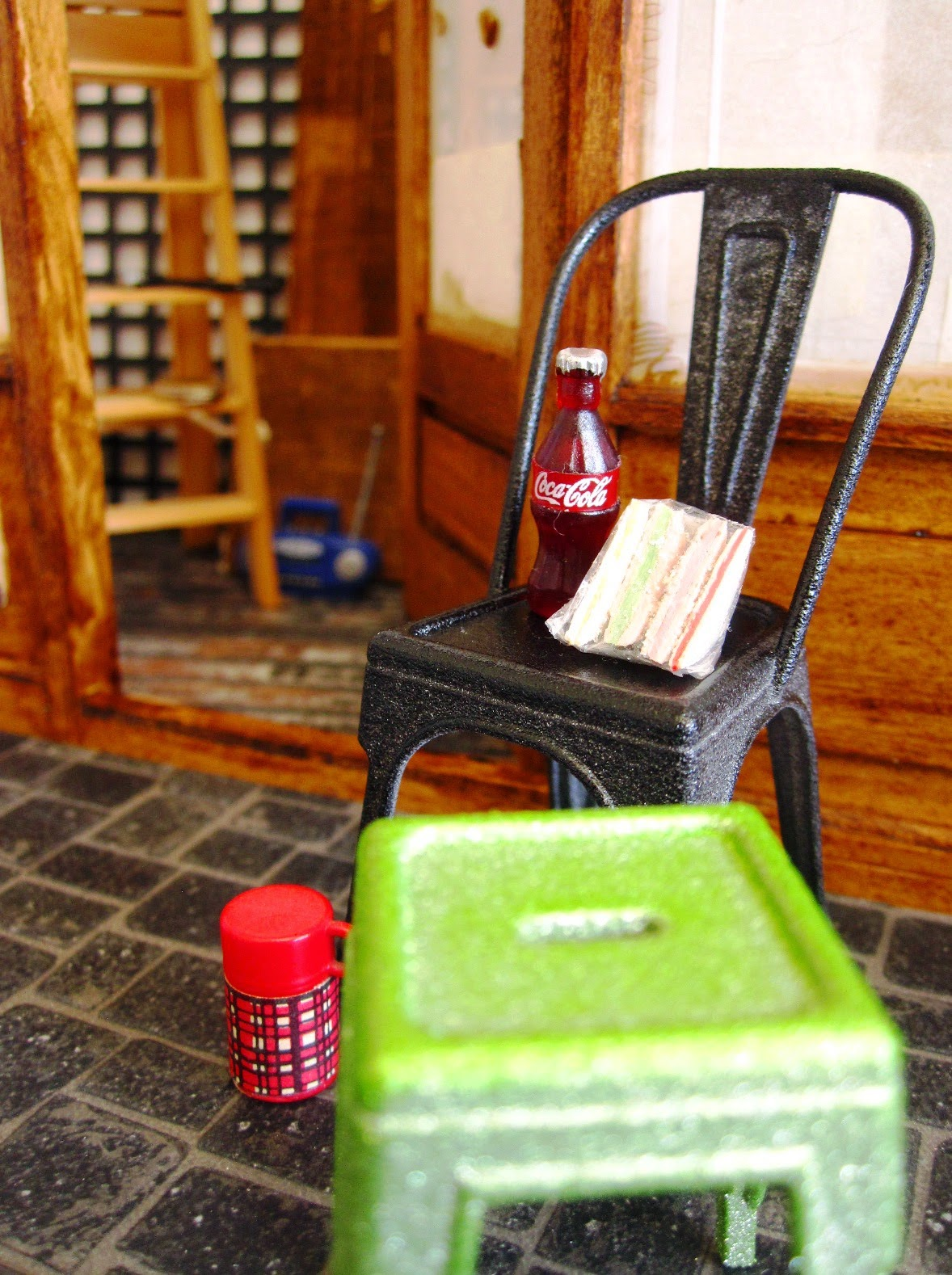 Dolls' house miniature builder's lunch on a cafe chair outside the front door of a cafe being renovated.