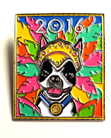 A close-up photo of the enamel pin. A white dog with black markings over its eyes is wearing a yellow mardi-gras headdress and a blue ribbon with a medal on it. The background features coloured feathers in a festive mix of aqua, yellow, lime green, hot pink and tangerine with a blue sky background.
