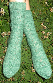 Someone wearing a pair of green socks. They have a lace leaf pattern along the leg and top of the foot.