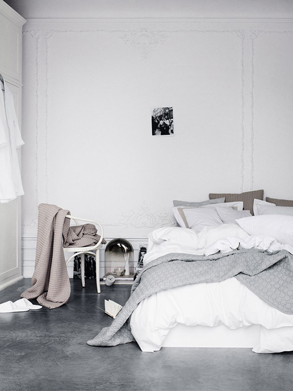 Monochromatic scandinavian bedroom with concrete floor and wall moldings. Photo by Line Klein
