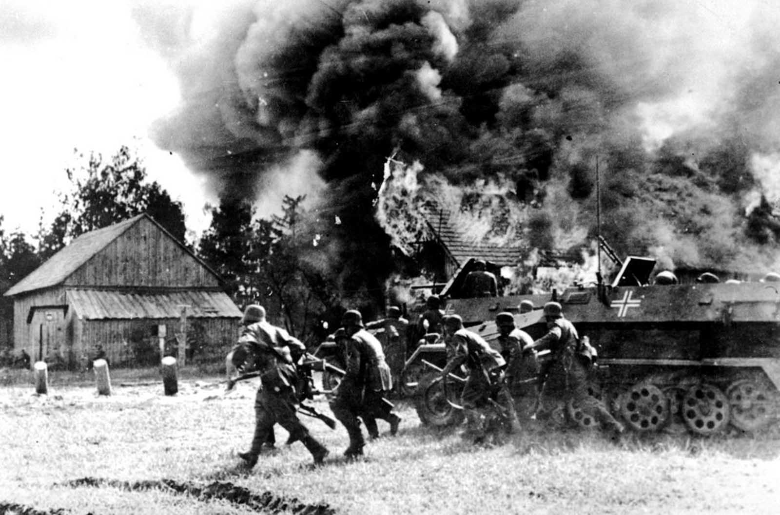 German soldiers, supported by armored personnel carriers, move into a burning Russian village at an unknown location during the German invasion of the Soviet Union, on June 26, 1941.