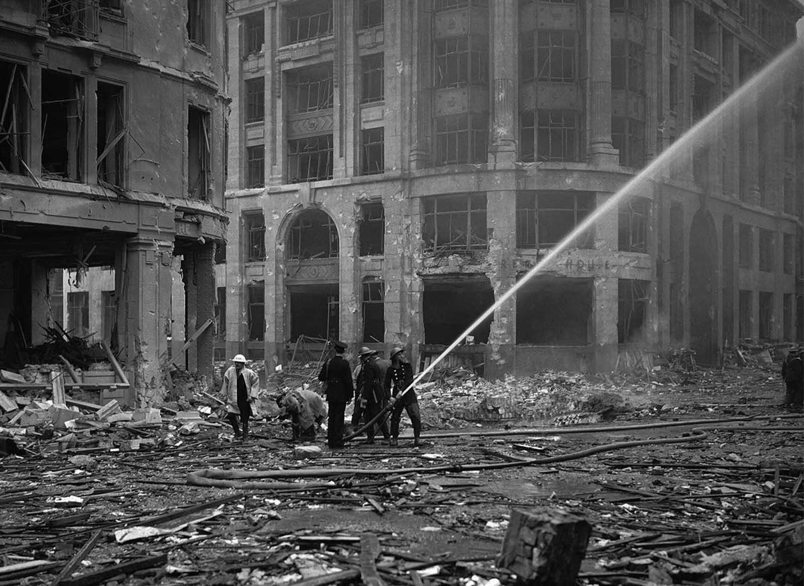 Firemen spray water on damaged buildings, near London Bridge, in the City of London on September 9, 1940, after a recent set of weekend air raids.