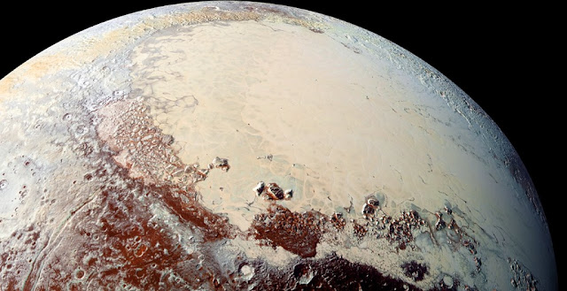 "This high-resolution image was captured by NASA's New Horizons spacecraft on its Pluto flyby in 2015, combining blue, red, and infrared images taken by the Ralph/Multispectral Visual Imaging Camera (MVIC). The bright region in the west is part of Pluto's ""heart"", and is rich in nitrogen, carbon monoxide, and methane ices.  Credit:  NASA/Johns Hopkins University Applied Physics Laboratory/Southwest Research Institute"