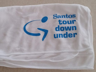 A folded white ice towel with the light blue Santos tour down under logo printed on it.