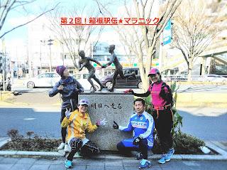 鶴見中継所の銅像を囲む4名のランナー