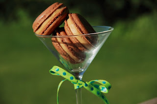 3 chocolate and peanut butter macarons stacked in a martini glass