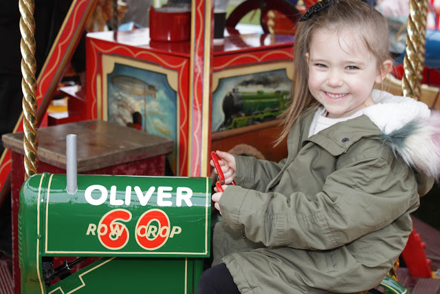 My niece smiling away, enjoying the Carters Steam Fair toy town ride.