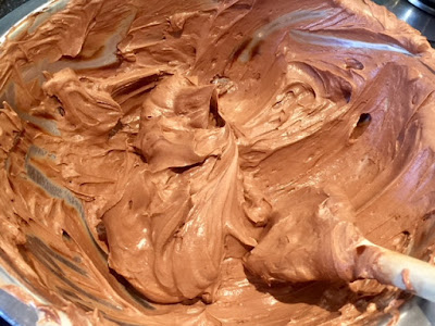 Chocolate, cream cheese and cream mixture in a silver bowl