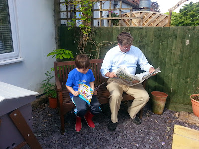 Grandad and grandson sitting on a bench, both reading.