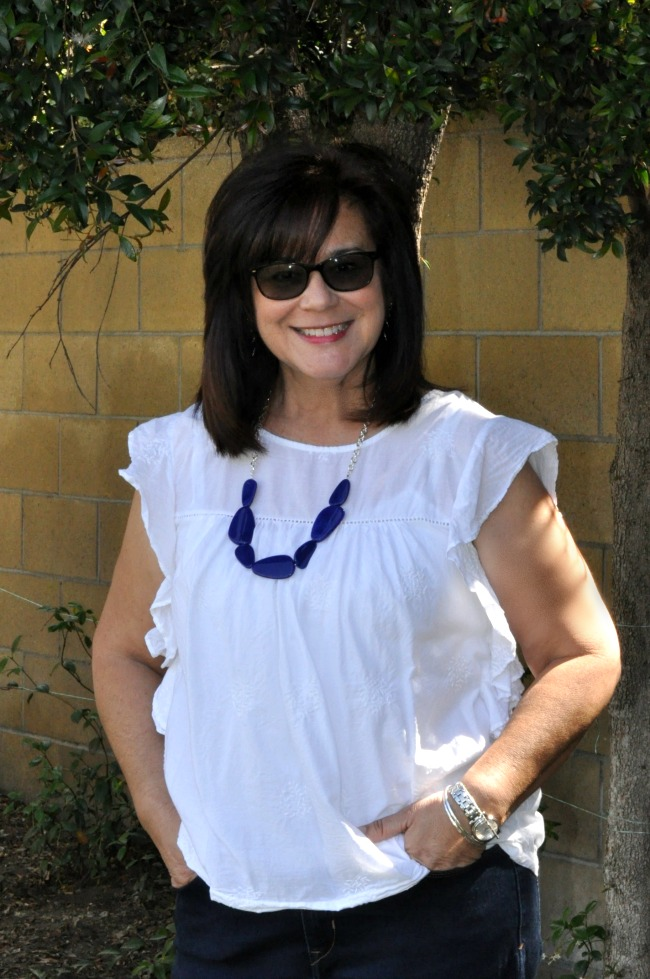 white blouse and blue statement necklace
