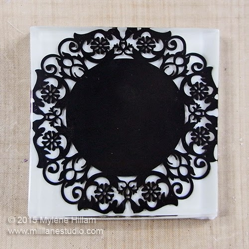 Square drink coaster made with a black pvc doiley embedded in clear resin against a bright white background.