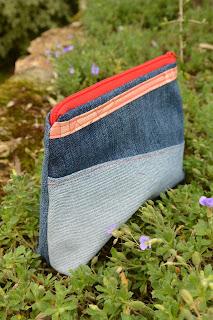 Trousse aux dimensions 17x14x5 cm approximativement. En matériaux jeans denim recyclés assemblés façon patchwork asymétrique, liseré tissu japonais, surpiqures rouge vif, fermeture éclair rouge, intérieur rouge bordeaux en coton unis. Les deux faces sont différentes.