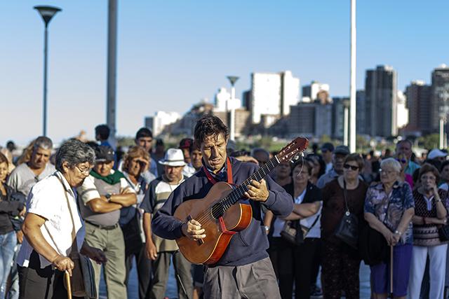 Una mujer pasa por detrás del músico que toca la guitarra en la Rambla.