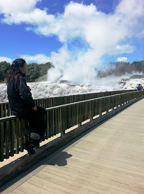 Man sitting on a railing of a bridge, watching tourists taking photos of a geyser.