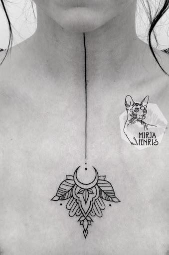 Uma linha preta corre o comprimento do utente do pescoço e leva a um projeto elaborado na foto do portador do peito em tinta preta.