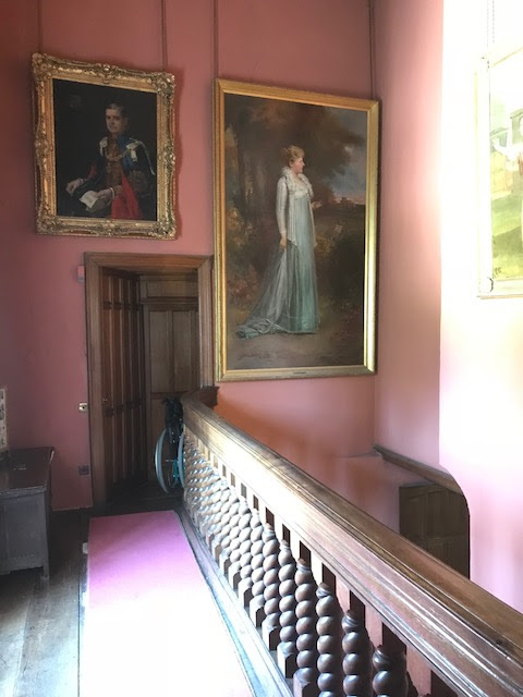 An upstairs hallway with paintings
