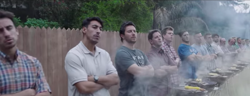 a still image from the Gillette commercial of a line of men standing in front of BBQs