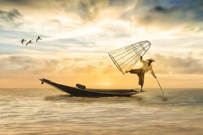 Asian fisherman balancing at the end of boat