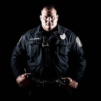 Large police officer standing with thumbs hooked onto belt at his hips, very serious look on his face.