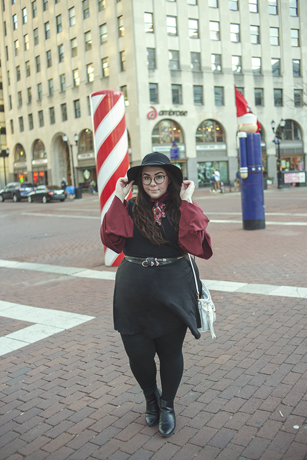 An outfit with a wide brim black floppy hat, maroon floral neck scarf, maroon triple tiered sleeve blouse, layered under a sleeveless black dress with a black circle skirt layered over top.