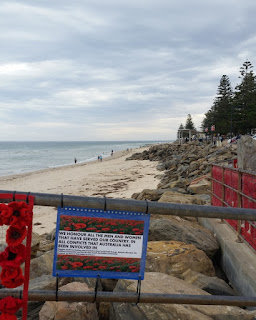 "Next to the ""We will remember them"" banner (the edge of which can be seen at leftt), is a dedication, the details of which can be read in a close-up photo elsewhere in this blog entry.  Behind the dedication are northerly views along the coastline. From left to right one can see the waters of St Vincents Gulf, people walking along the beach, a rocky foreshore and a line of Norfolk pine trees marking the esplanade.  In the foreground on the right hand side, is the rear view of the ""Lest we forget"" and ""Anzac"" banners which are facing the esplanade."
