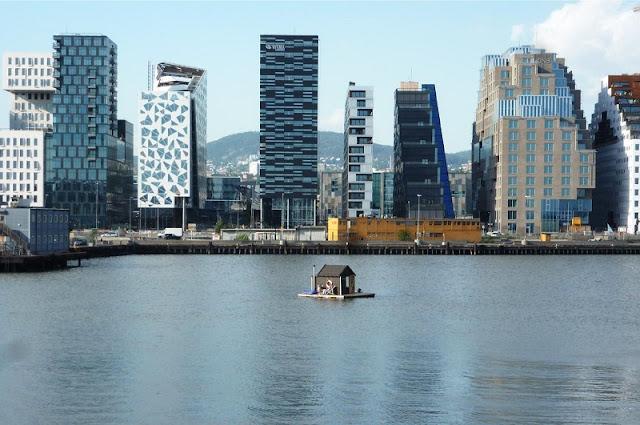 Cool foto de una pequeña casa flotante en un lago, al fondo la ciudad llena de rascacielos.