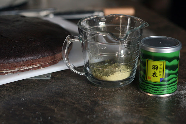 A glass measuring cup with some matcha green tea powder sitting beside a can of green tea powder.