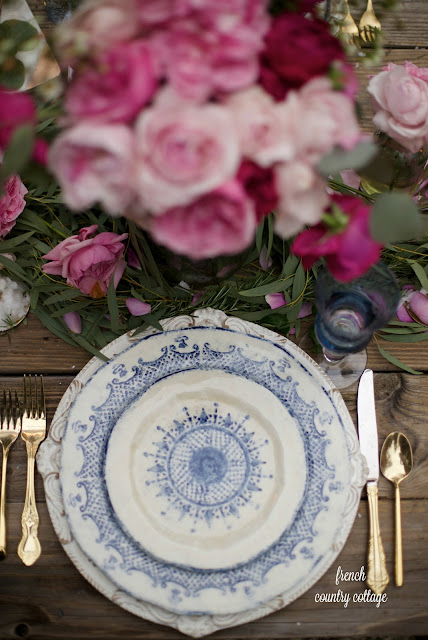 Table setting with blue and white dishes and pink flowers
