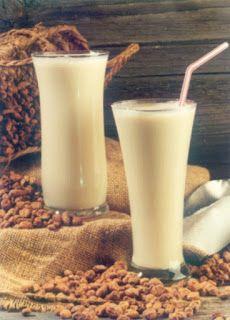 Horchata. Dos vasos con bebida veraniega sobre una bolsa de arpillera, con semillas alrededor.