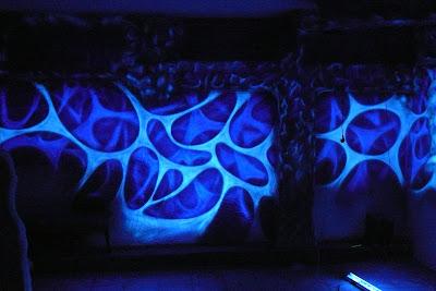 Mlowanie ściany w klubie farbami fluorescencyjnymi, malowidło świecące w ciemności, efekt świecenia ścian
