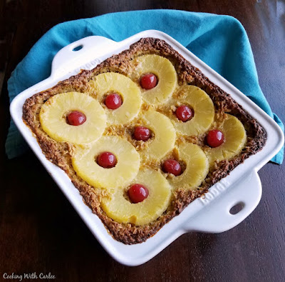 square pan filled with baked oatmeal topped with pineapple and cherries