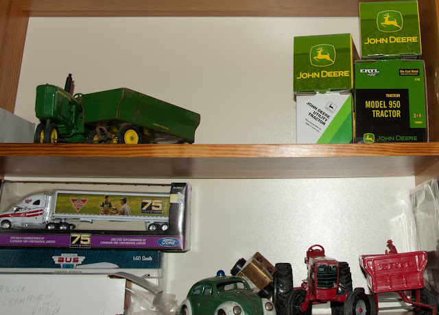 A few more JD toys stacked on high on a shelf.