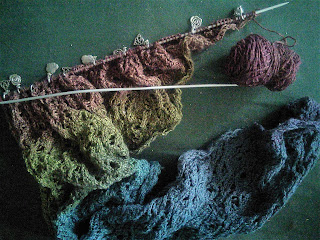 A lace shawl on a set of straight needles.  The yarn is a gradient from blue to red, and there is a small amount of yarn left in the cake of yarn.  There are a number of stitch markers with silver charms looped around the needles.