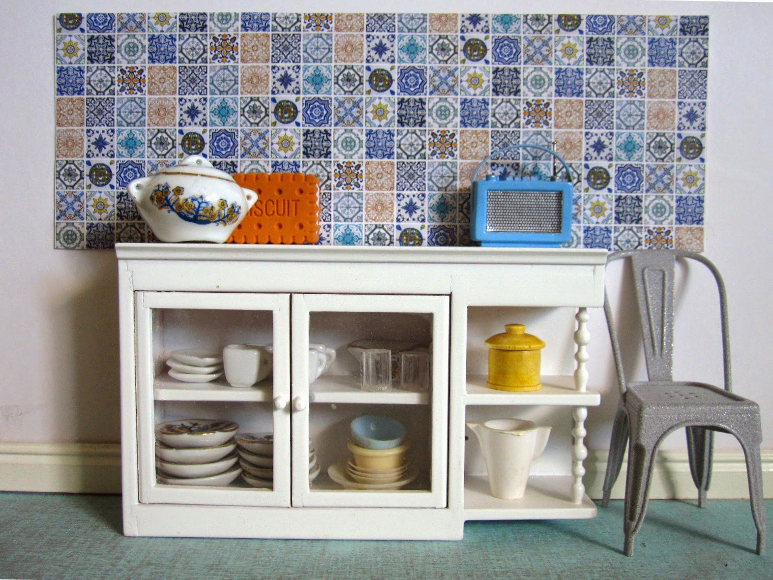 Modern dolls house miniature kitchen scene with a white glass-fronted cupboard full of crockery in front of a wall tiled with various blue and white tiles. Next to teh cupboard is a french cafe chair and on top is a tureen, a giant ornamental biscuit and a Roberts-style radio in blue.