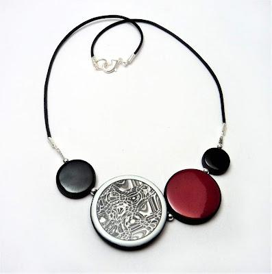 Insoupçonnable collier graphique rouge noir et motifs noir et blanc de créateur