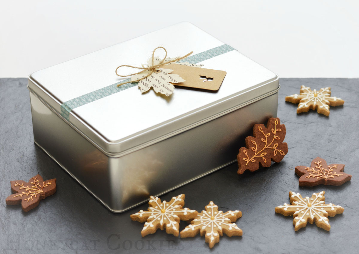 Gift tin decorated with tags, containing Honeycat Cookies' three sugar cookie flavours: gingerbread, chocolate, vanilla. Photo by Honeycat Cookies
