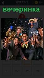 Группа молодых людей на вечеринке отдыхают  и веселятся в конфети и рюмки в руках