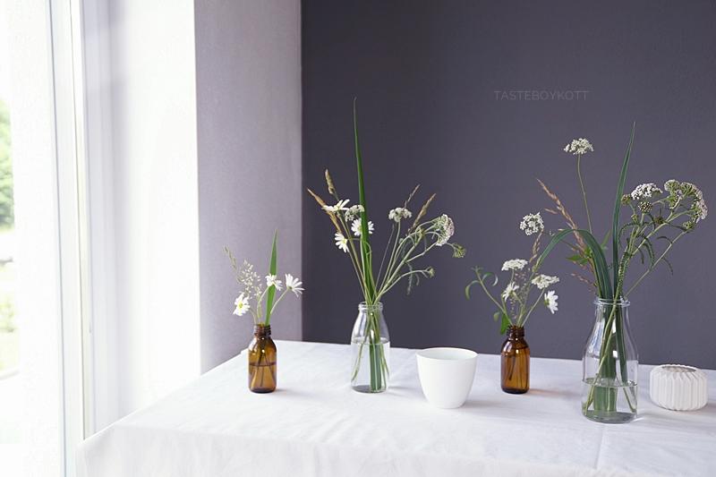 Den Tisch für ein Abendessen sommerlich dekorieren mit Margeriten, Giersch, Gräsern und Zweigen in Glasflaschen und einer weißen Tischdecke | Tasteboykott