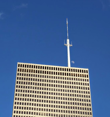 Top portion of One Shell Office Building with antenna and moon