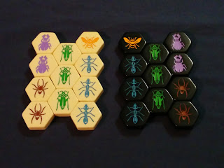 The twenty-two pieces from the base set: the eleven white pieces on the right and the eleven black on the left. Each set is a thick Bakelite hexagonal tile with an arthropod embossed into the top and paint poured into the recessed area. On each side, there are two purple beetles, two brown garden spiders, three green grasshoppers, three blue worker ants, and one queen bee.
