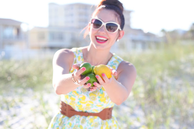 Woman in Lemon Dress holding lemons and limes