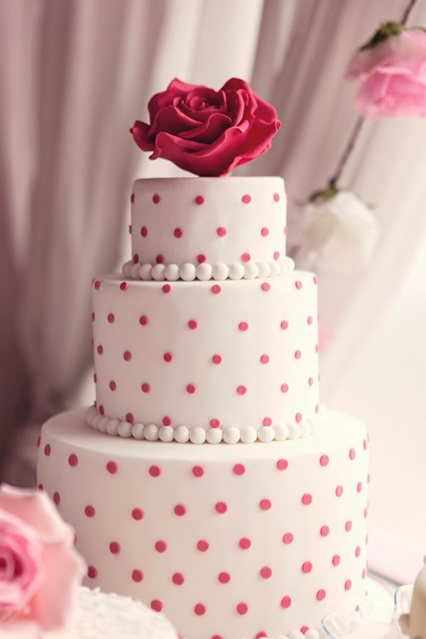 A tiered polka dot cake with extra large sugar craft rose