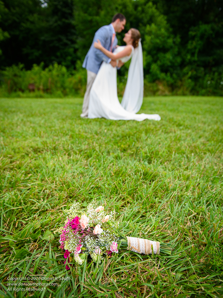 a photo of a wedding couple with the bride's bouquet on the ground
